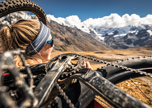 Young woman enjoying the view with bike on the back, Val Forni, Valfurva, Lombardia, South Tyrol, Italy