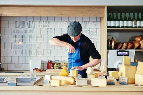 Käsehändler schneidet Käse mit Käsedraht, umgeben von einer Vielzahl von Käsesorten auf der Arbeitsplatte
