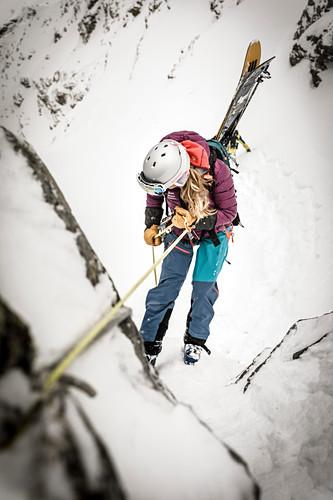 Junge Frau seilt mit Ski von einem Felsblock ab, Stubaier Alpen, Tirol, Österreich