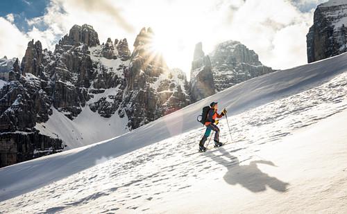 Skitourengeherin wirft Schatten im Aufstieg bei Gegenlicht, Brenta Gruppe, Italien