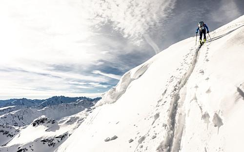 Skitourengeherin zieht eine steile Aufstiegsspur an einer Wechte vorbei richtung Gipfelkamm, Alpbach Tal, Tirol, Österreich