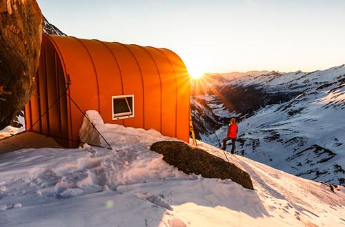 Junge Frau genießt den Sonnenuntergang neben einer Biwak Schachtel im winterlichen Hochgebirge, Günther Messner Biwak, Pfitschertal, Südtirol, Italien