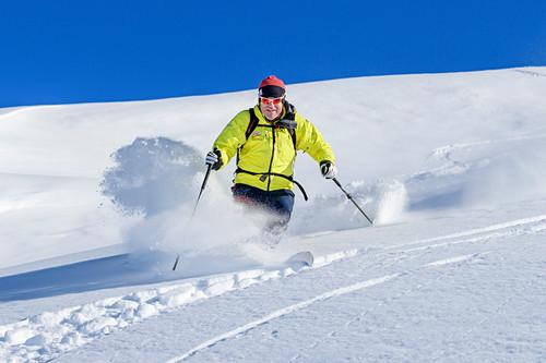Mann auf Skitour fährt durch Pulverschnee ab, Regenfeldjoch, Kitzbüheler Alpen, Tirol, Österreich