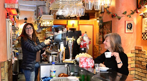 Woman as barrista and guest drinks at cafe, bar in Sicily, Italy