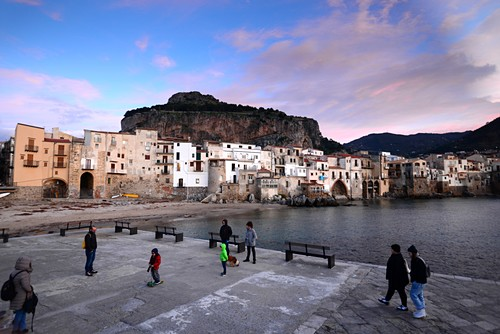 Evening on the beach of Cefalu with its old waterfront houses under the rock, north coast, Sicily, Italy