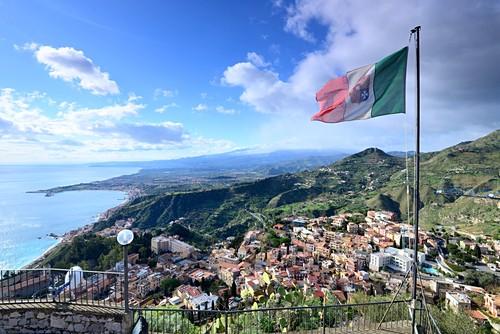 Italian flag and view and sea and coast, Santuario Madonna della Rocca, Taormina, east coast, Sicily, Italy