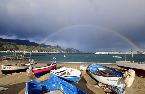 Boats and rainbows on the beach at Giardini Naxos below Taormina, east coast, Sicily, Italy
