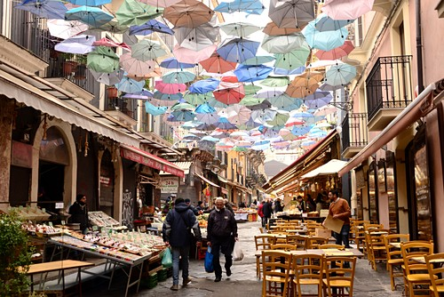 Alley with umbrellas in the market and restaurant terrace, Catania, east coast, Sicily, Italy