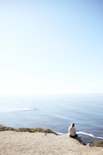 Junge Frau sitzt an einer Klippe und blickt auf den Pazifik am Rand des Highway 1, Big Sur State Park, Kalifornien, USA.