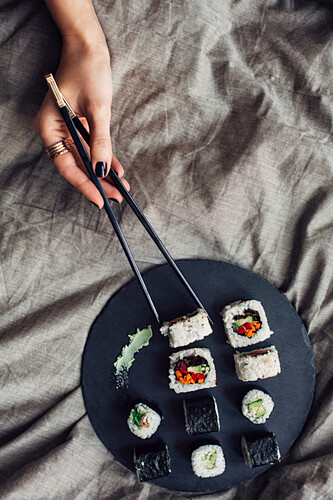 Hands of woman reaching for platter of sushi on bed