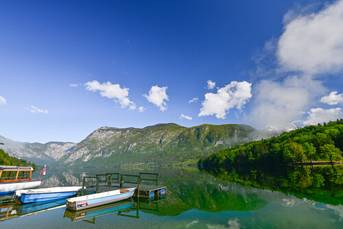 boats and reflection at Lake Bohinj, with mountains and wood in the background, Ribcev village, Stara Fuzina, Bohinj, Gorenjska, Julian Alps, Triglav National Park, Slovenia, Europe