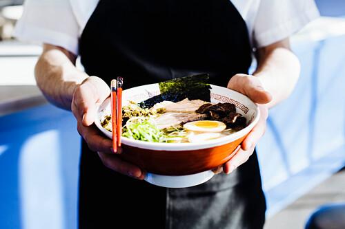 Chef holding bowl of ramen in restaurant