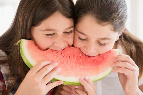 Caucasian twin sisters eating watermelon
