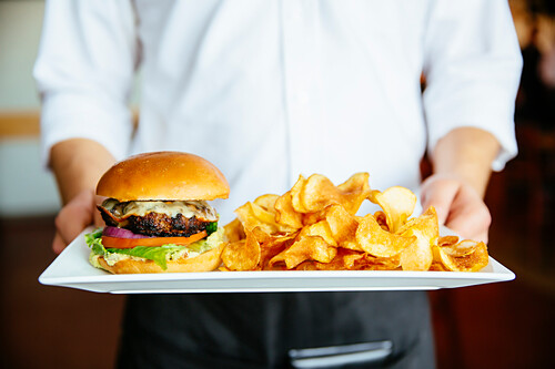 Caucasian waiter holding plate of cheeseburger and chips