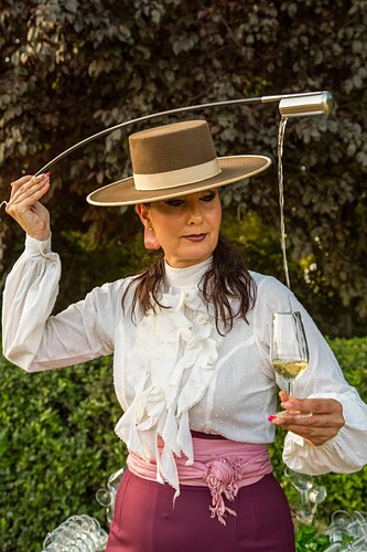 Woman pouring sherry wine from the barrel using venencia. Malaga. Costa del Sol, Andalusia southern. Spain Europe.
