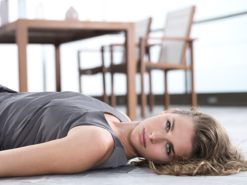 Young Woman lying on her back, looking into the camera