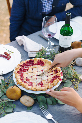 Woman serving pie at outdoor table