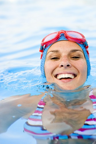 Woman in bathing cap and goggles in swimming pool