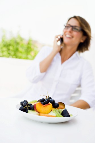 Plate of fruit, woman using mobile phone in background