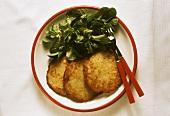 Three potato pancakes with corn salad