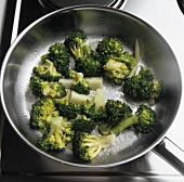 Sweating blanched broccoli in a frying pan