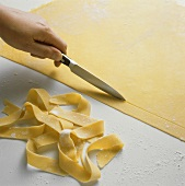 Cutting ribbon pasta from rolled-out pasta dough