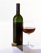 Eine Flasche (ohne Etikett) und ein Glas Rotwein, Korken