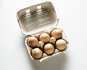 Six eggs in a box; one egg broken