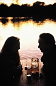 A Couple Enjoying Beer near the Water