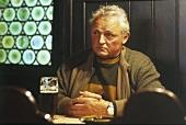 Man sitting pensively in front of dark beer