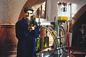 Oliven zu Öl verarbeiten : Arbeiter prüft das frische Öl