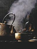 Decorated tea bowl; teapot; statue of Buddha