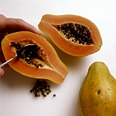 Scraping out papaya seeds with a spoon