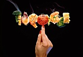 Shrimp and Vegetable Skewer Held by a Finger