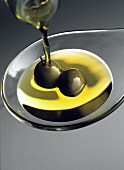 Pouring Olive Oil onto Spoon with Olives