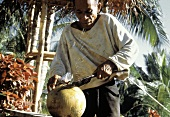 Asian Man Opening a Coconut with a Knife