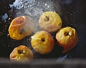 Small baked apples on black baking sheet