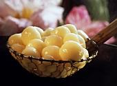 Rice flour balls in coconut milk in a wire ladle