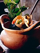 A Ladle Scooping Seafood Soup Out of a Clay Pot