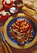 Ein Teller mit Lammkoteletts auf Paprika-Mais-Gemüse