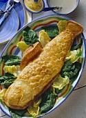Lachsforelle im Teigmantel (Fischform) auf Salatblättern