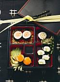 Mehrere verschiedene Sushi in eckigen Schalen angerichtet