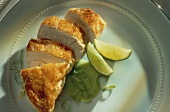 Sliced chicken breast with lime wedges