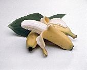 Partially Peeled Banana with an Unpeeled Banana