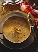 Peanut soup with celery in brass bowl