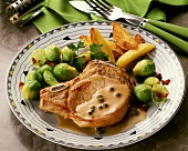 A pork chop in pepper sauce with brussel sprouts & potatoes