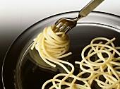 Gekochte Spaghetti mit einer Gabel aufdrehen