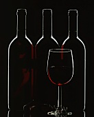 Silhouette of three red wine bottles and one red wine glass