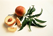 Whole Peach and a Sliced Peach with Peach Leaves