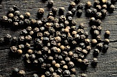 Many Black Peppercorns on Wood Surface